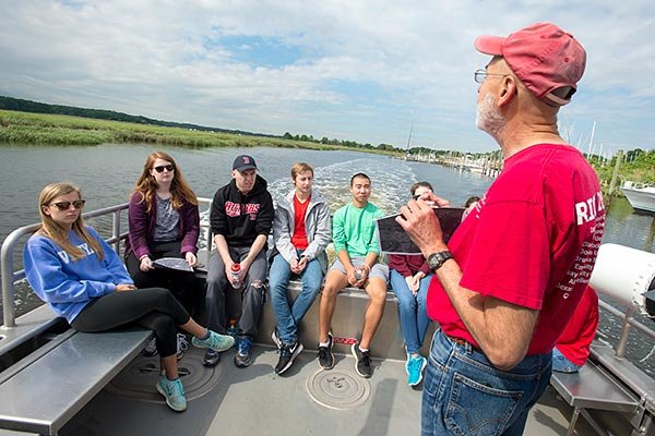 Professor and students on a boat.