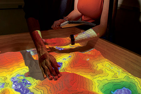 Two hands in an agmented reality sandbox.